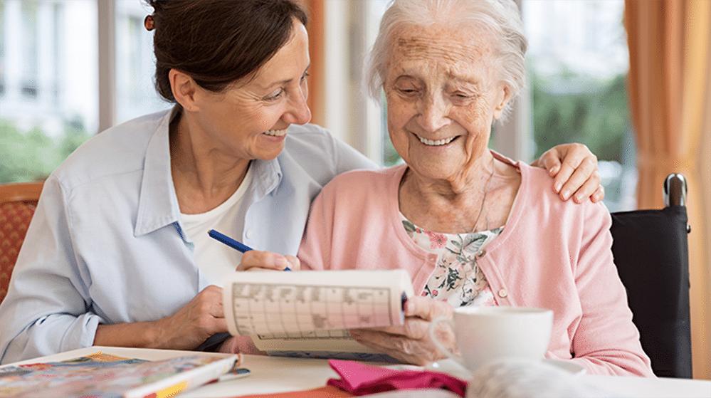 Pflegerin und ältere Frau lachend am Tisch