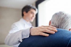Mann legt älterem Mann Hand auf die Schulter