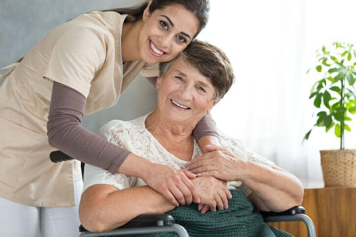 Pflegerin und alte Frau im Rollstuhl lächelnd