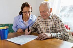 Pflegerin sitzt mit altem Mann an Formularen