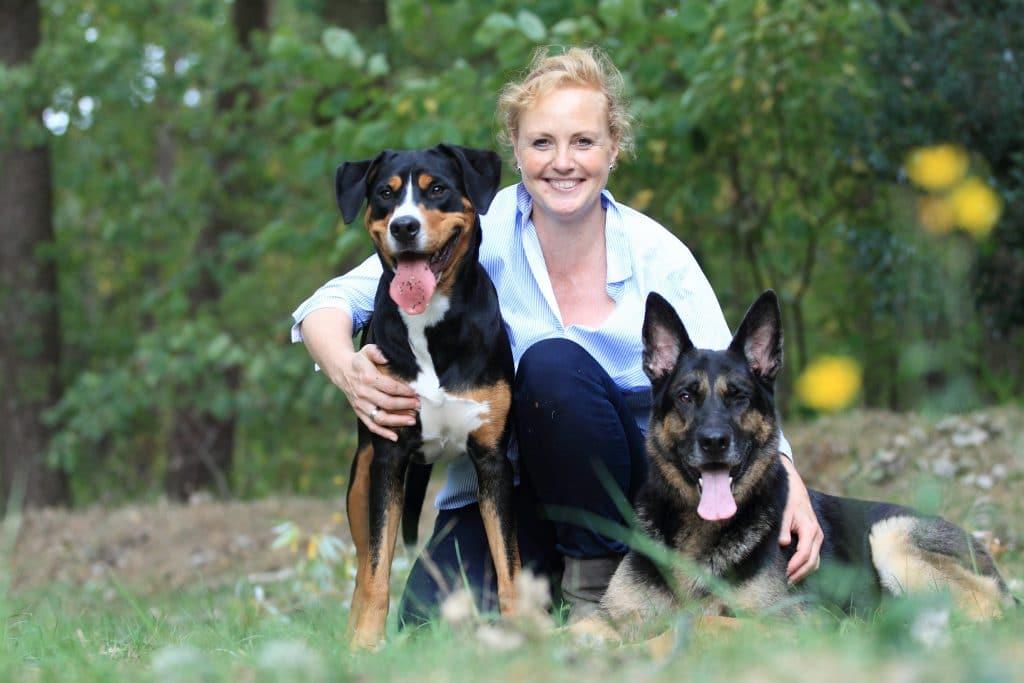 Frau kniend mit zwei Hunden vor sich