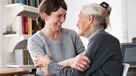 Pflegerin sitzt lachend mit älterer Frau