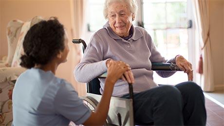Pflegerin kniet vor älterer Frau in Rollstuhl
