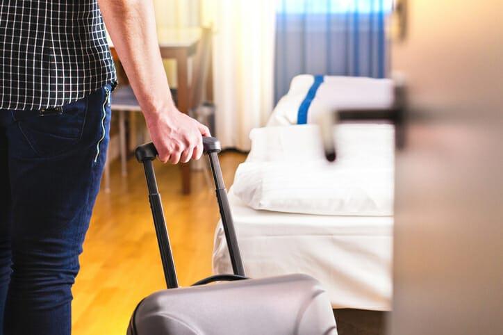Frau zieht sich Koffer in ein Zimmer