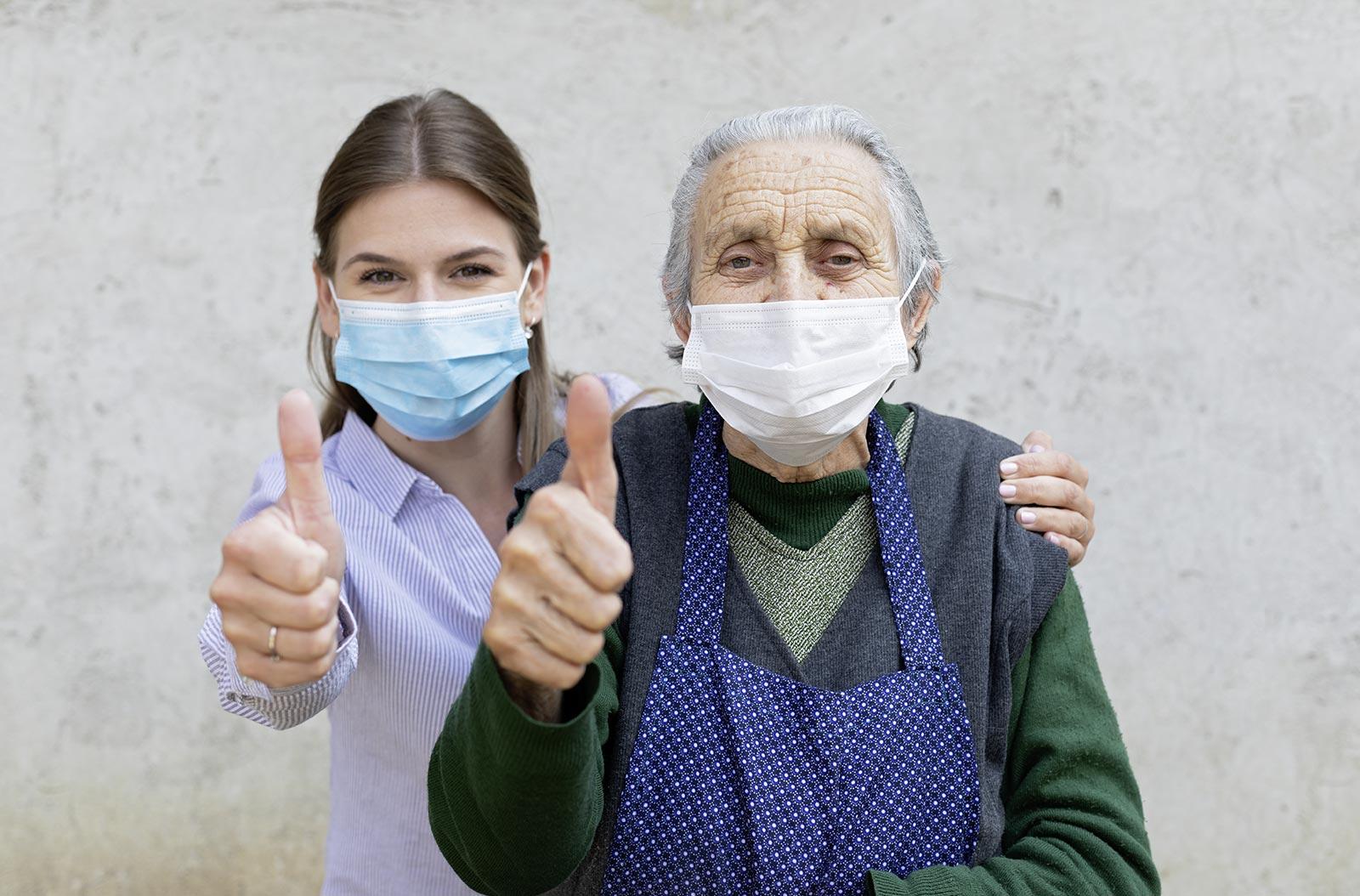 Pflegerin und ältere Frau mit Maske und Daumen hoch