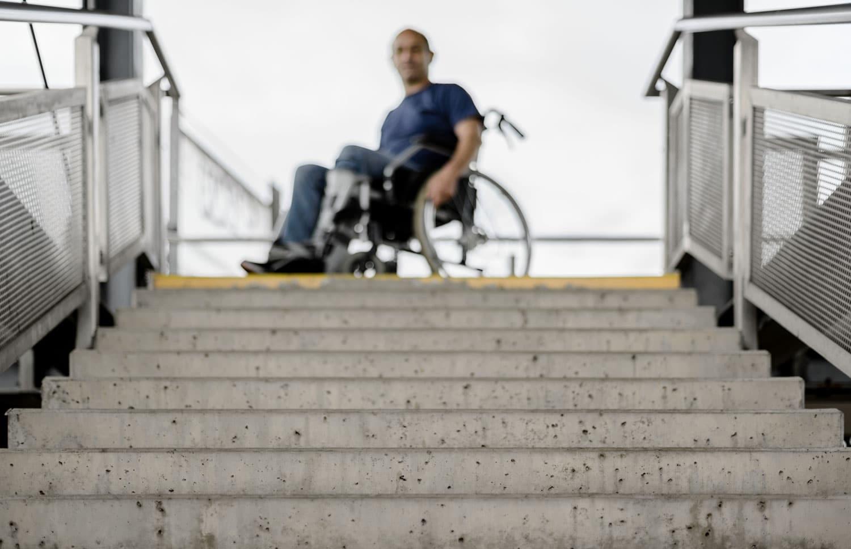 Mann im Rollstuhl am oberen Ende von Treppen