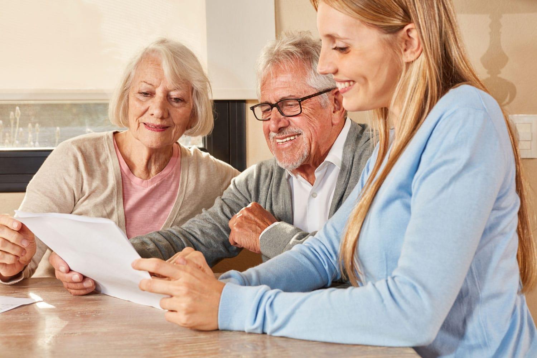 Rentner-Paar lachend mit Pflegerin am Tisch