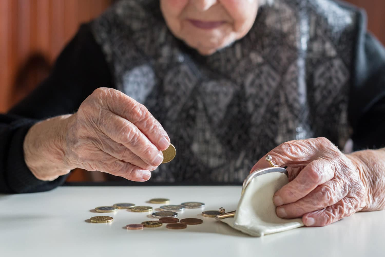 Alte Dame zählt ihr Münzgeld im Portemonnaie