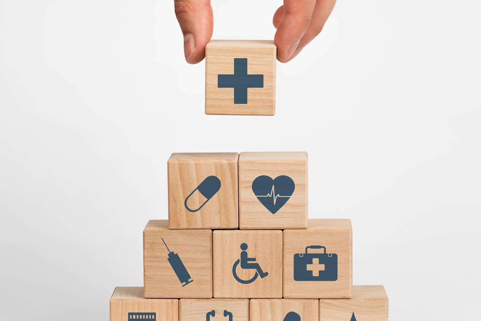 Bausteine mit Pflegesymbolen aufeinander gebaut