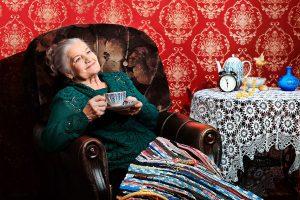 Ältere Dame sitzt lächelnd mit Tee im Sessel