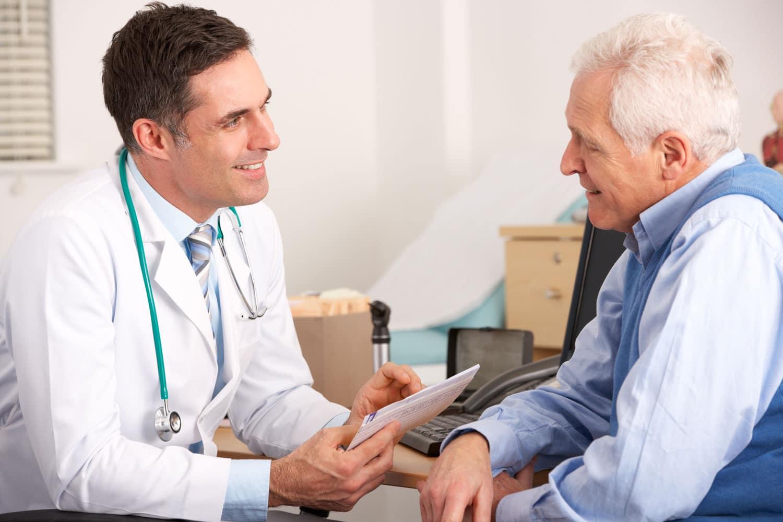 Arzt berät lächelnd einen älteren Herrn
