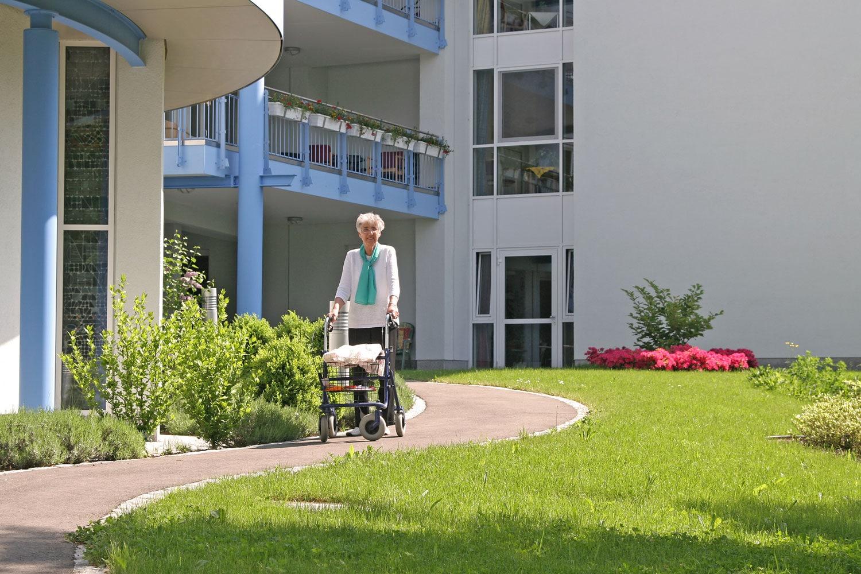 Alte Dame mit Rollator vor einem Pflegeheim
