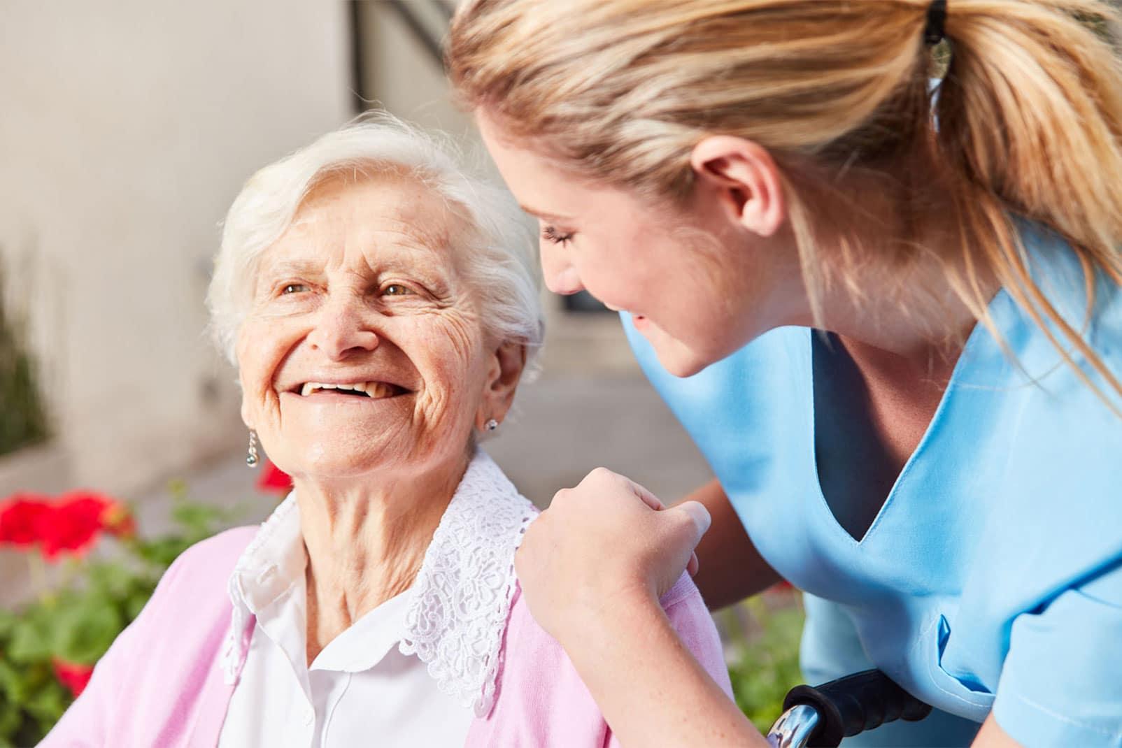 Pflegerin legt lachender Dame die Arme um