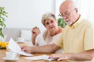 Ehepaar diskutiert über Dokumenten am Tisch