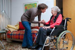 Frau redet mit alter Frau in Rollstuhl