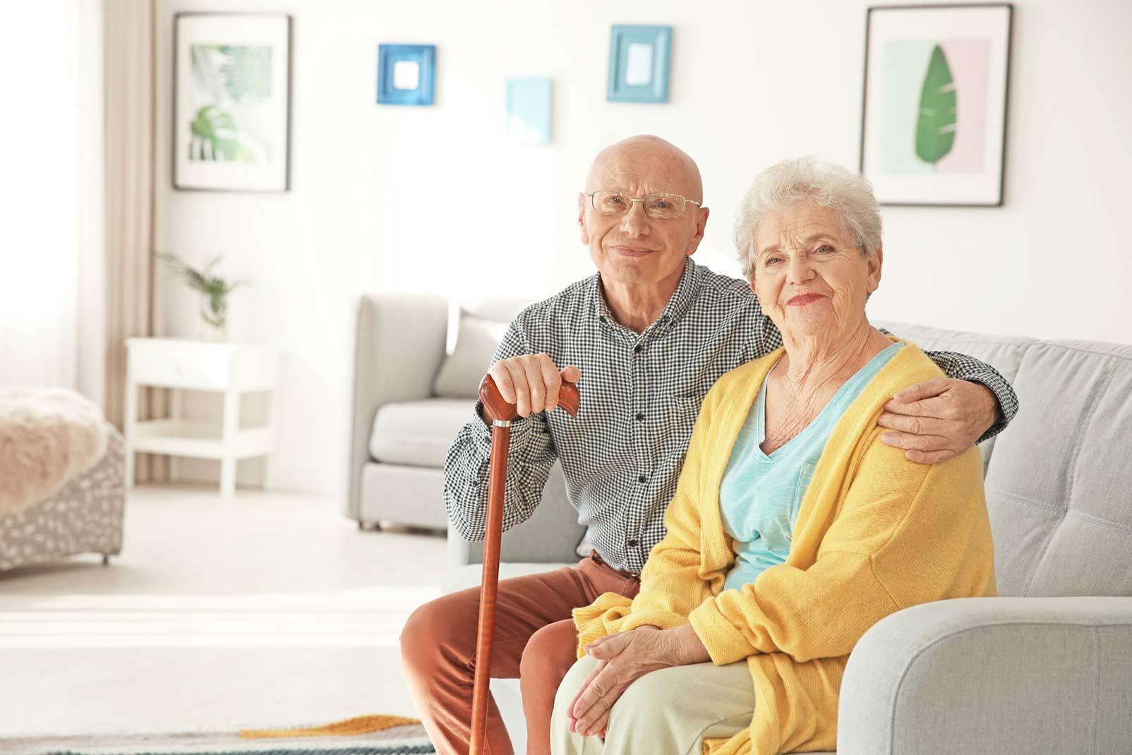 Altes Ehepaar sitzt lächelnd auf Couch