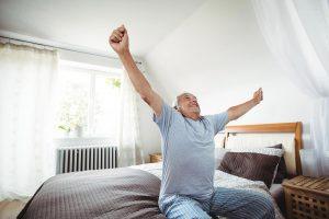 Mann streckt sich auf Bett vor Aufstehen