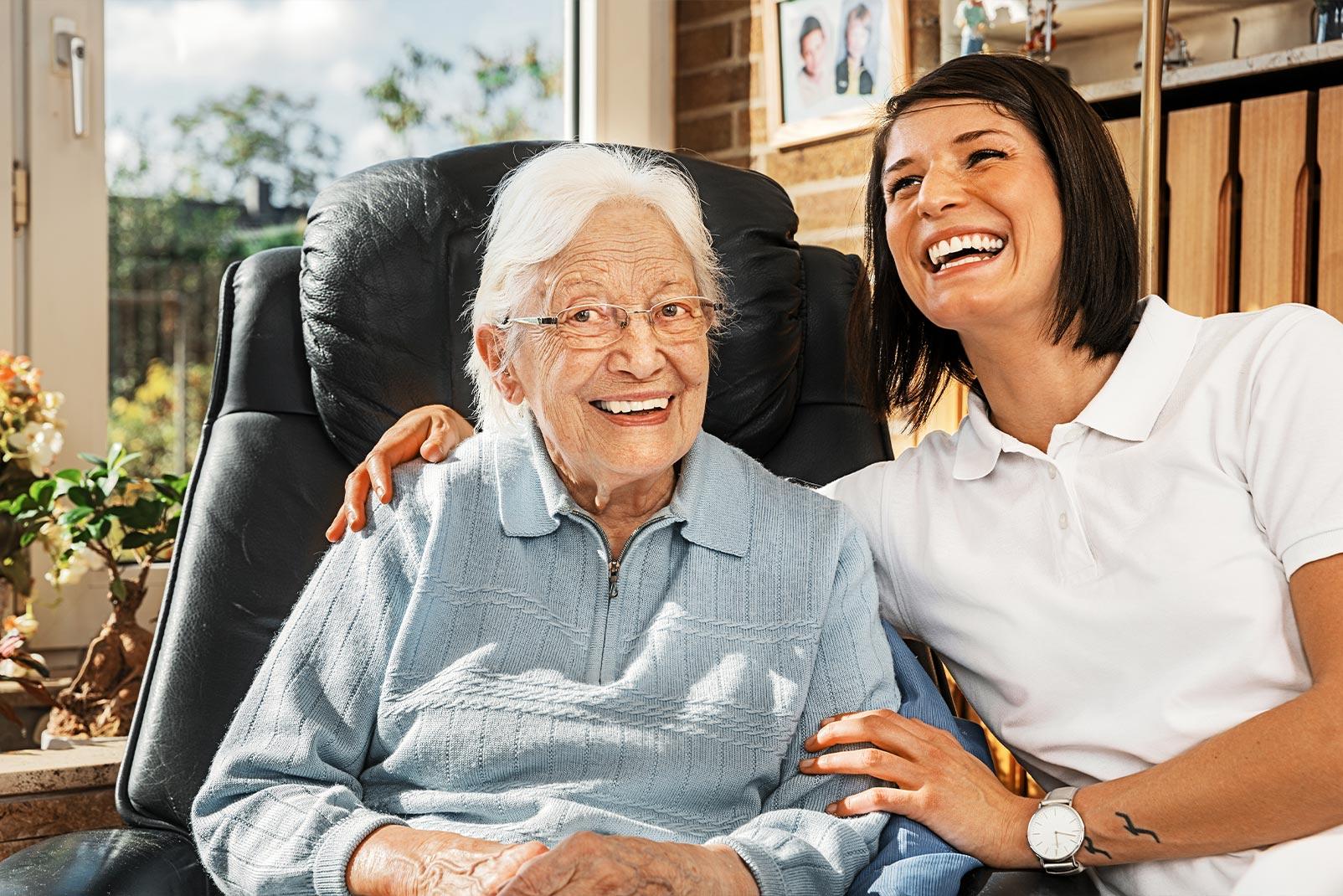 Pflegerin lacht mit Dame im Sessel