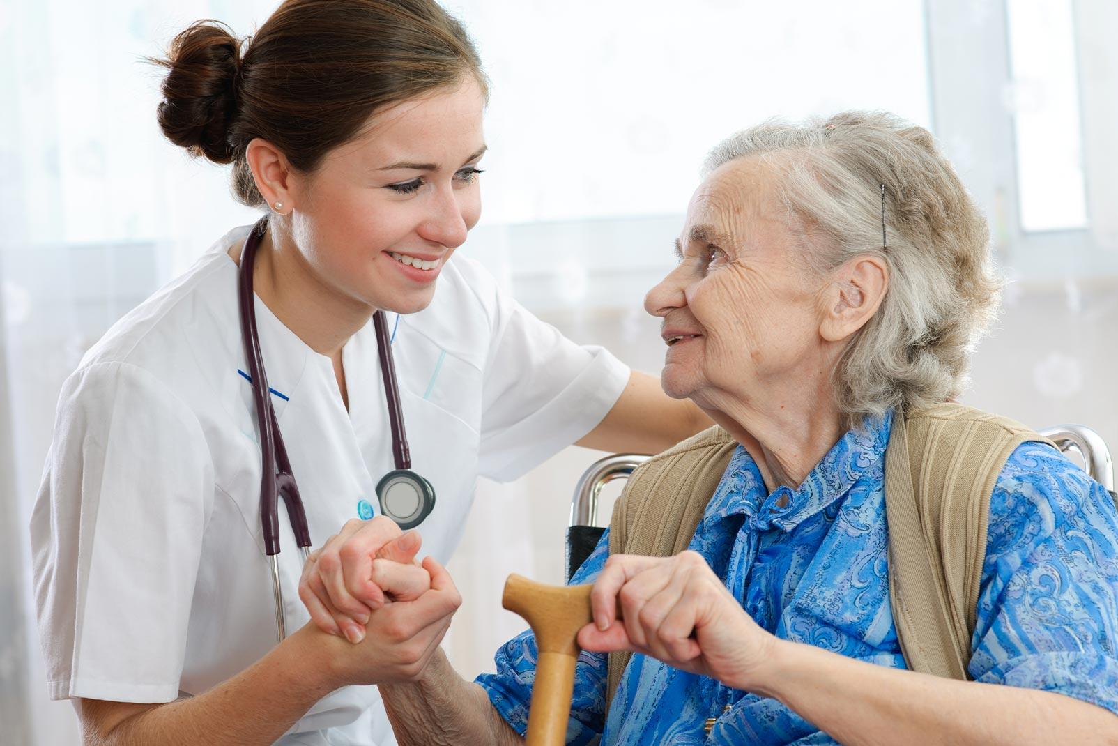 Pflegerin mit Stetoskop hält ältere Frau