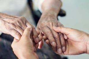 Zwei Hände halten zwei faltige Hände
