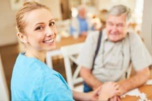 Polnische Pflegerin mit altem Mann an Tisch