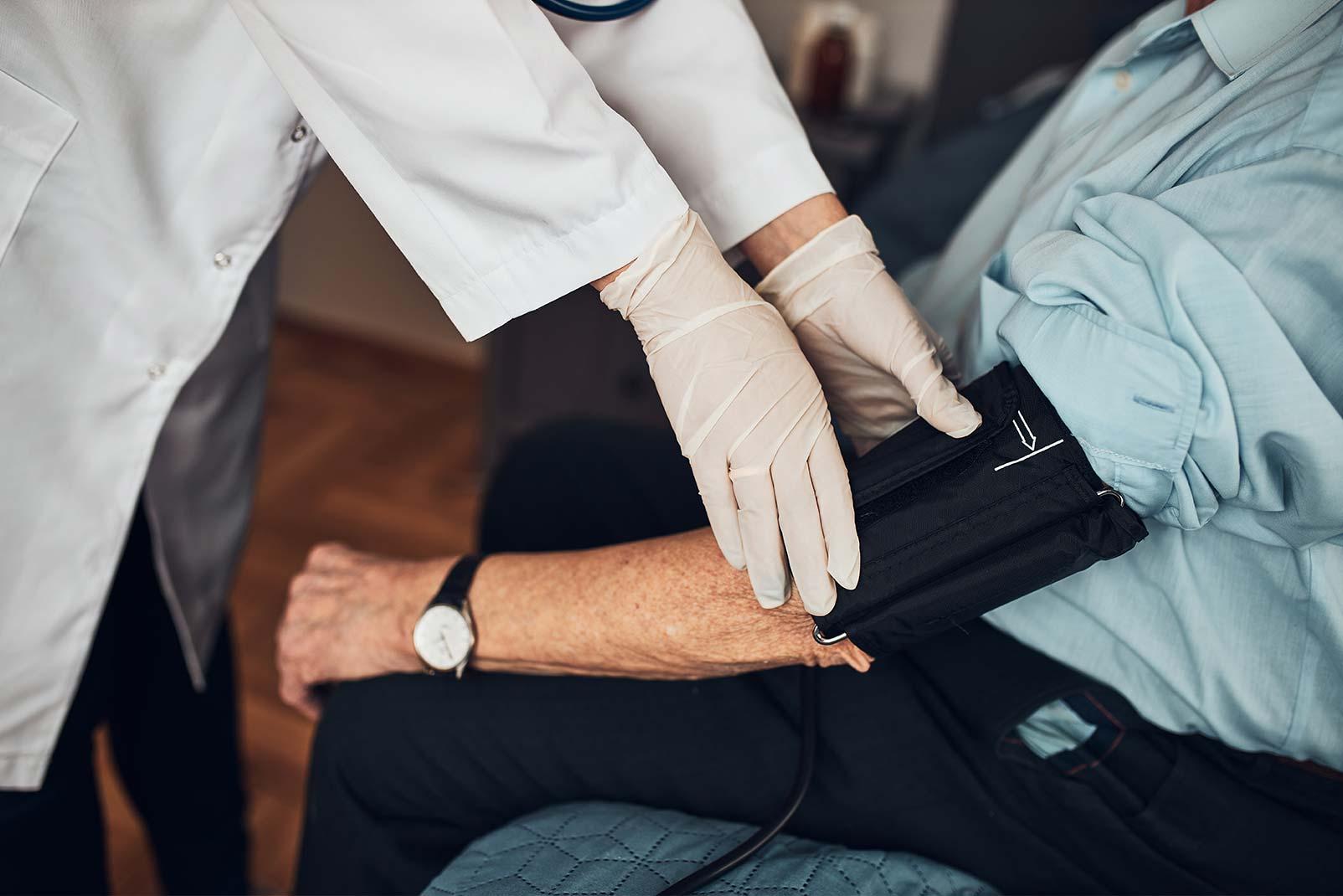 Arzt nimmt Blutdruck bei älterem Mann