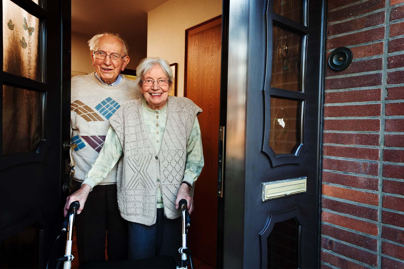 Altes Ehepaar steht in ihrem Hauseingang