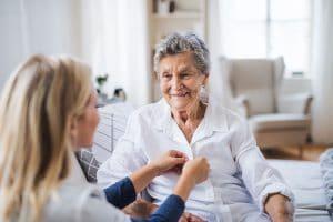 Pflegerin knöpft Frau die Bluse zu