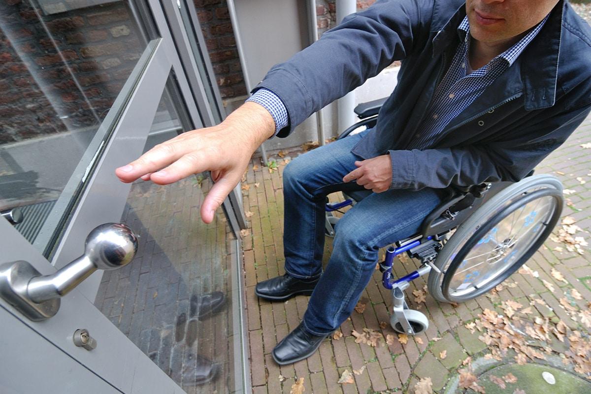 Mann im Rollstuhl greift nach Türknauf