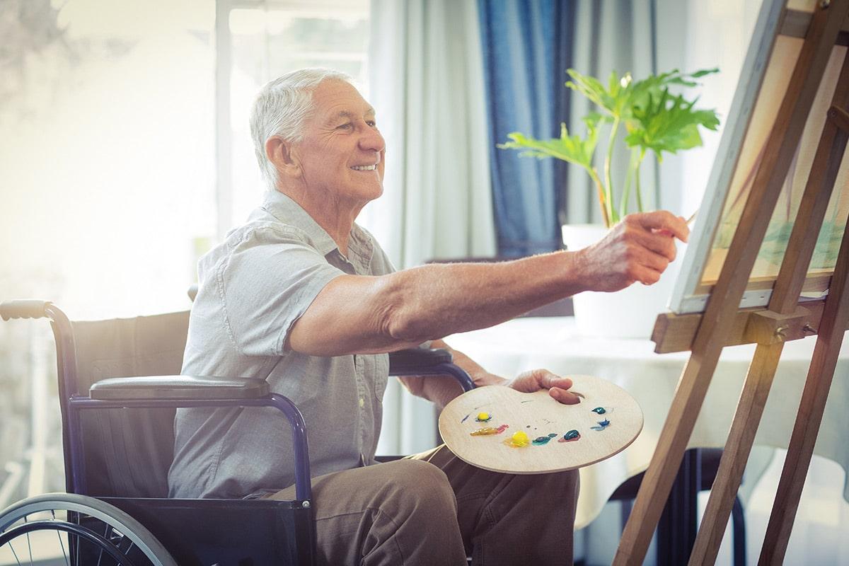 Mann im Rollstuhl malt auf Leinwand