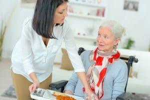 Pflegerin stellt Frau in Rollstuhl Essen hin