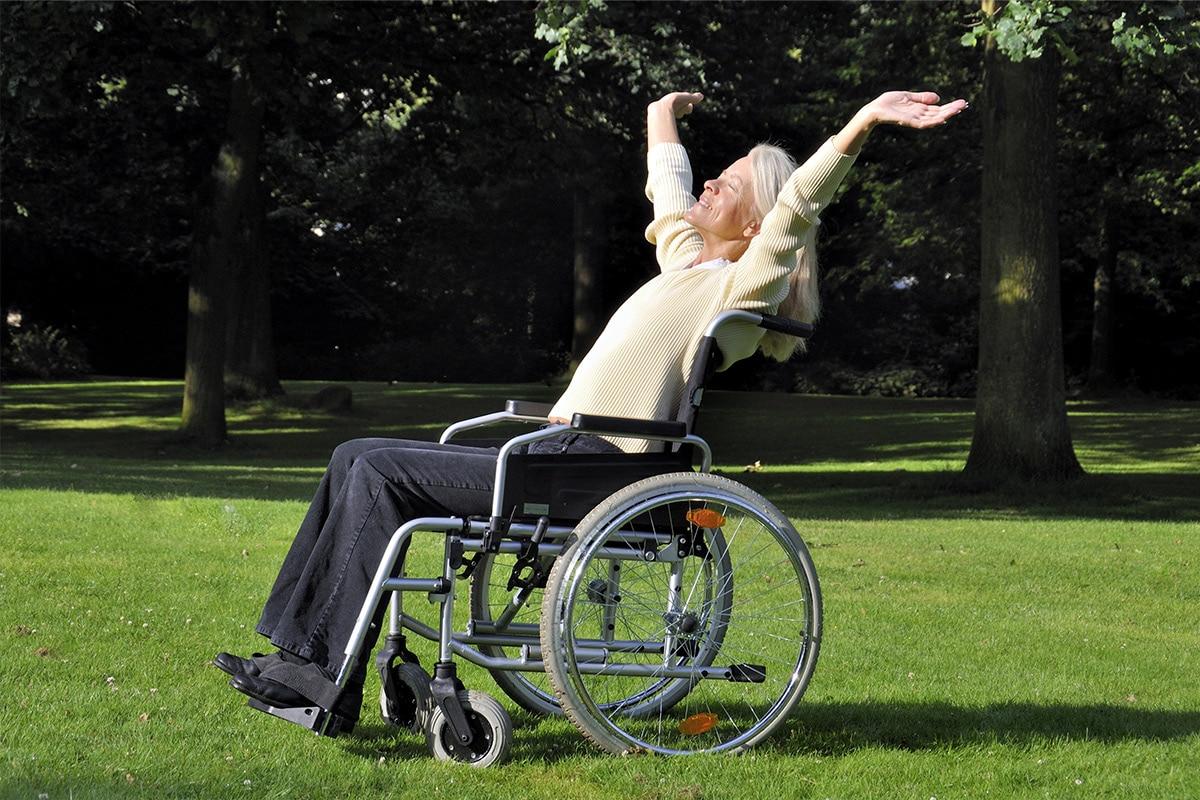 Frau mit Hände hoch in Rollstuhl draußen