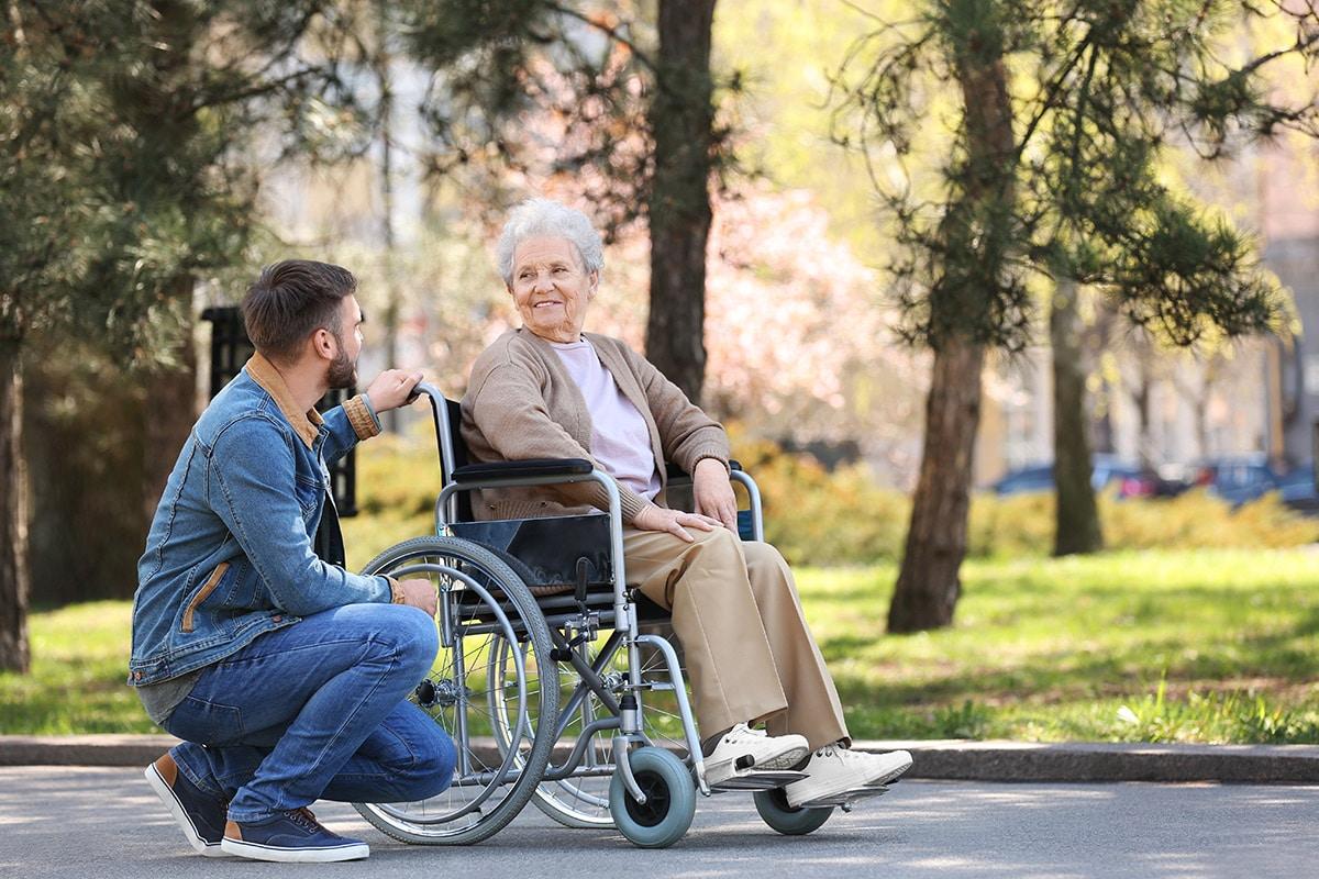 Mann kniet draußen vor Frau in Rollstuhl