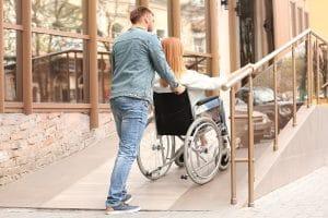 Mann schiebt Frau die Rollstuhlrampe hoch