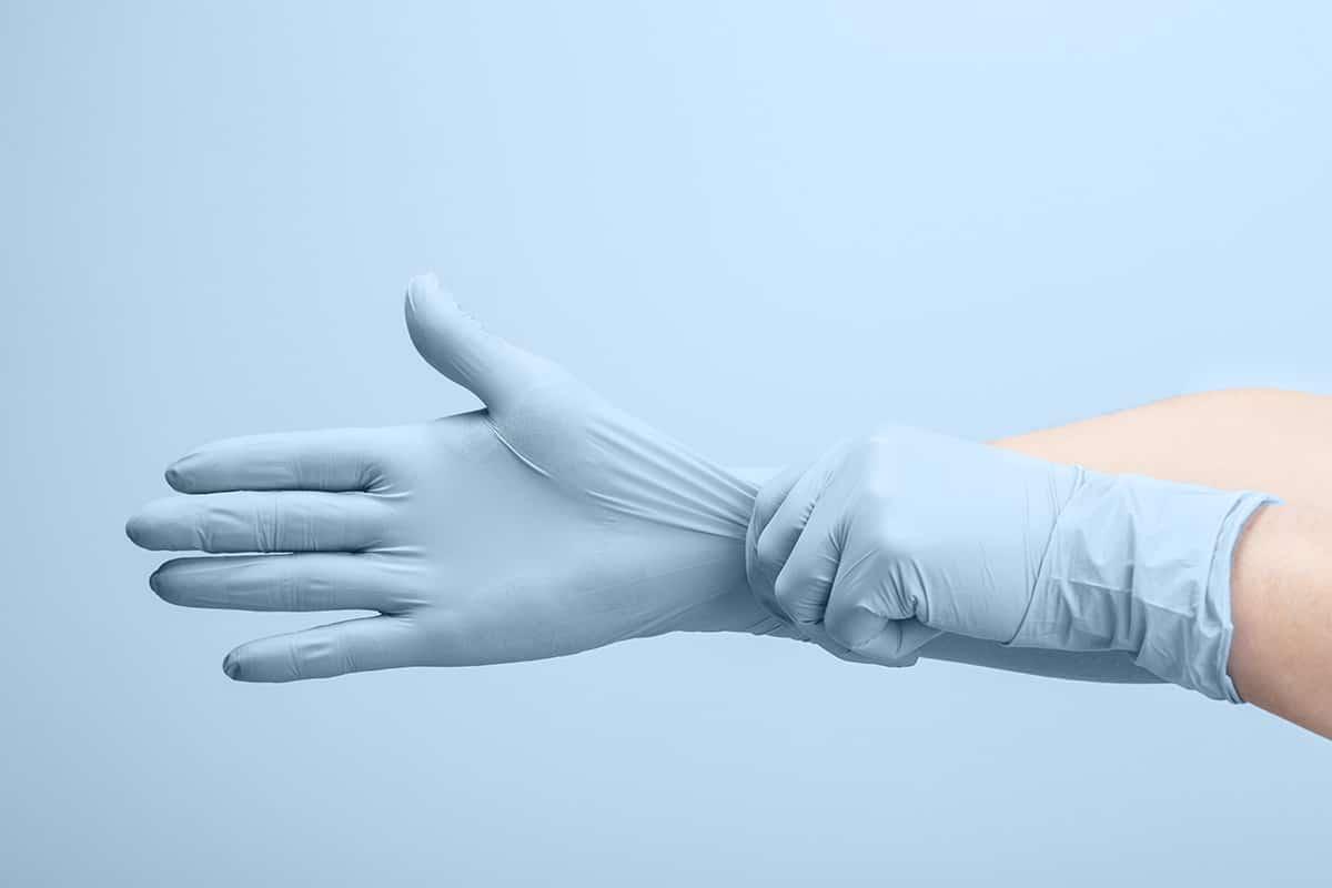 Hände in medizinischen Handschuhen