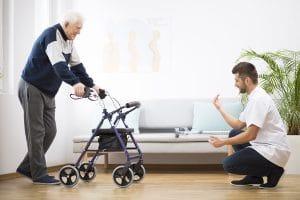 Mann motiviert alten Mann am Rollator